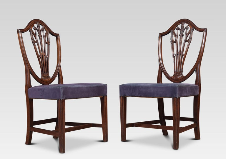 A set of ten very good quality mahogany Hepplewhite style dining chairs. Having pierced wheatsheaf carved splats above upholstered overstuffed seats the upholstery has some marks but is serviceable. All raised up on square tapering front legs