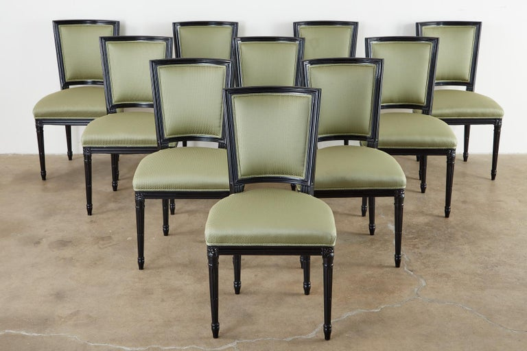 Dramatic set of ten black lacquered dining chairs made in the grand French Louis XVI taste. Attributed to Maison Jansen from the estate of Roger Prigent Malmaison, New York. Upholstered with a pistachio green fabric having gilt specks. The frames