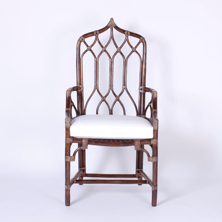 Rare set of ten dining chairs with an exotic cathedral or gothic form, graceful bentwood lines wrapped with reed at the joints, and custom cushions. Casually elegant, sturdy, comfortable, and signed McGuire on a brass plaque.   Measures: