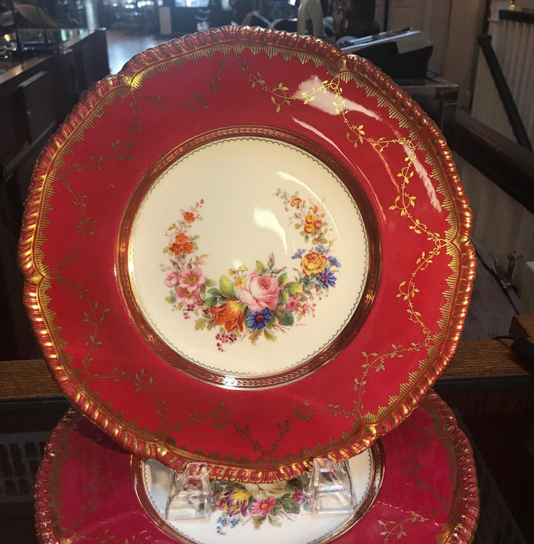 A set of ten hand-painted and gilt service dinner plates by Minton, England. The hand-painted porcelain plates with floral garlands and berry red borders with gilt overlay. Each one signed by the artist E. Ellis. Each one with the Minton mark and