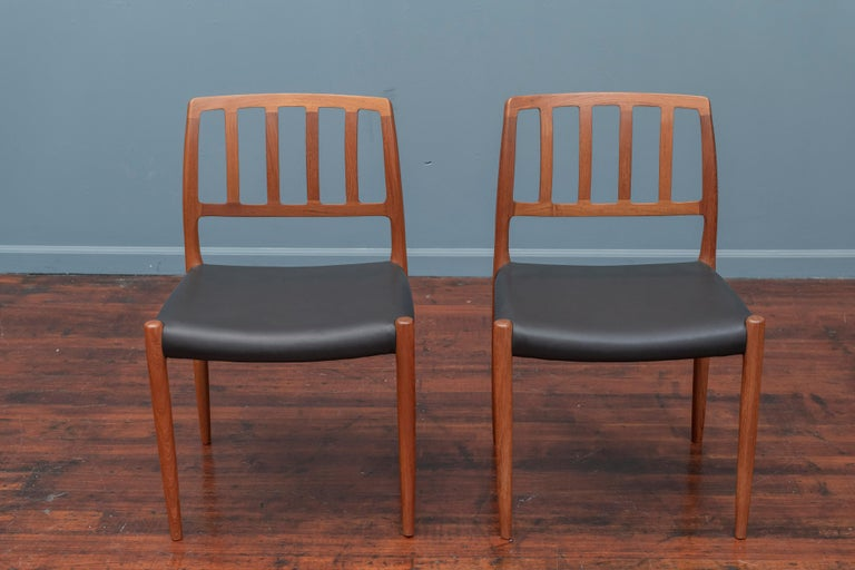 Set of ten Niels Otto Moller for J.L. Moller model 83 teak dining chairs newly upholstered in Italian black leather.