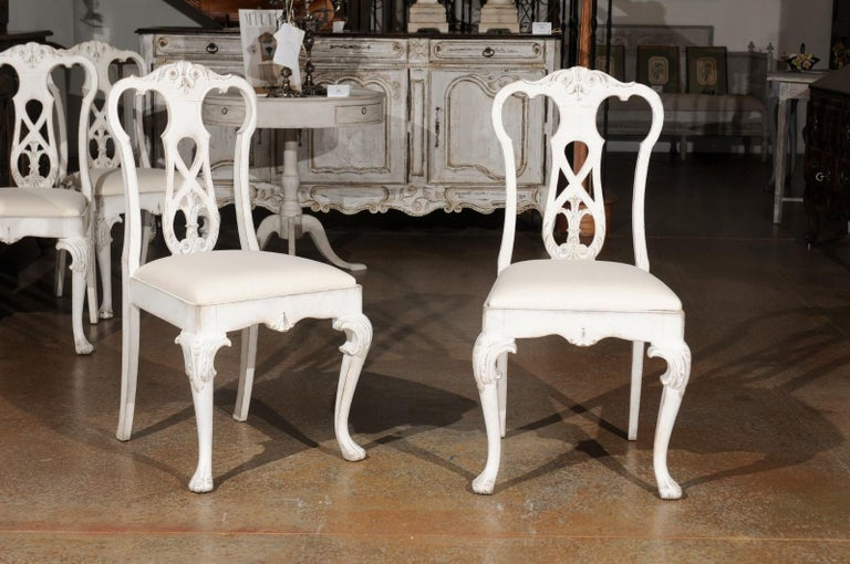 A set of ten Scandinavian Rococo style painted wood dining room side chairs from the 20th century, with carved splats, cabriole legs and new upholstery. Created in Scandinavia, each of this set of ten dining chairs features a carved splat adorned