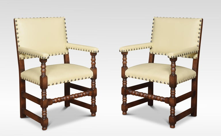Set of ten carved dining chairs the square leather close nailed backs above overstuffed seats the carvers with padded arms all raised up on turned front legs united by stretchers. Dimensions: Armchairs Height 37 inches height to seat 19