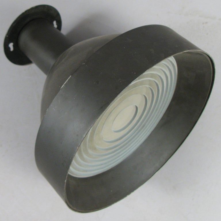 A set of three 1950s enameled ceiling lights by Lightolier, with thick glass shades with concentric design. Labelled Lightolier. In original condition with age appropriate wear.
