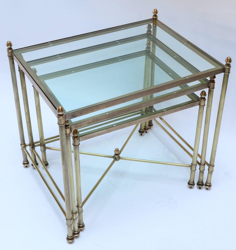 Set of three 1960s Italian brass nesting tables with finials and decorative details.  Measures: Large: 19in x 14in x 18.5in high Medium: 17in x 13in x 16.5in high Small: 115in x 112in x 14.5in high.