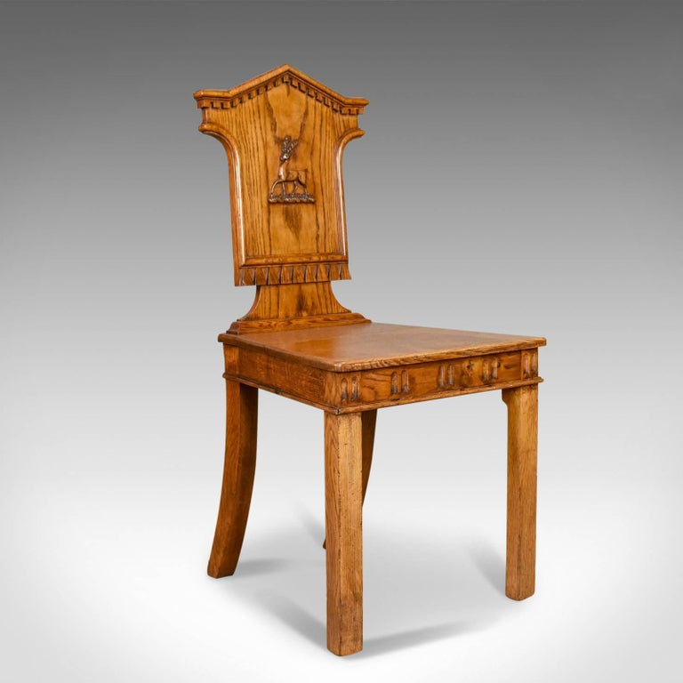 This is a set of three antique hall chairs in oak, Scottish displaying stag emblems from the Regency period and dating to circa 1820.  Attractive honey hues to the well figured oak Solidly jointed with a wax polished finish Of quality