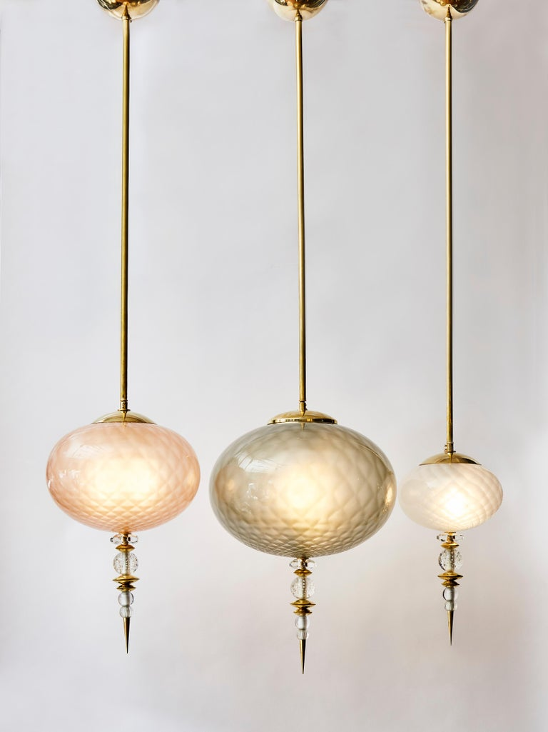 Set of three charming suspensions made of brass structures and different colored Murano glass globes.