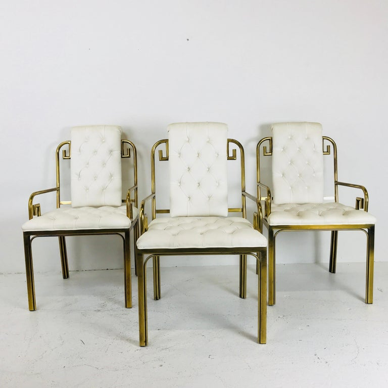 Set of three brass Greek key chairs by Mastercraft. Chairs are in good vintage condition but recommend refinishing brass plating and new upholstery.  Dimensions: 20.5