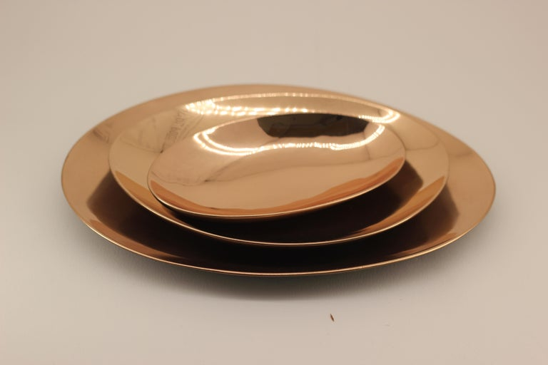 Set of three handmade cast bronze plates with a polished finish. Cast using very traditional techniques, they are polished revealing the lustrous finish of this noble material.