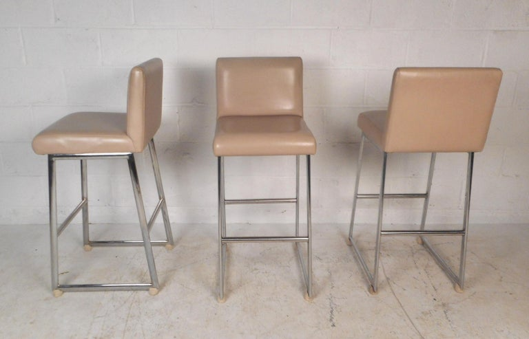 A stunning set of three vintage modern bar stools with chrome frames and thick padded seating covered in beige vinyl. The unique slipper design offers a comfortable and stylish place to sit. This beautiful mid-century set of bar stools make the