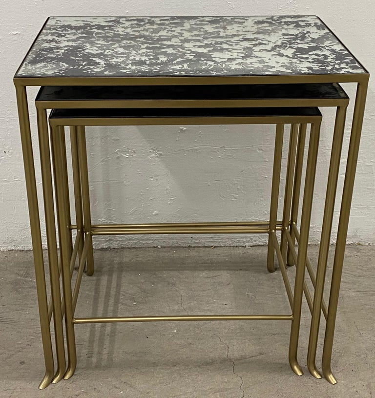 Set of three contemporary brass plate steel and flecked mirror nesting tables  These contemporary tables have a Classic mid modern touch.  The tables nest for easy storage. Pull one, or both out for an extra surface when your friends or family