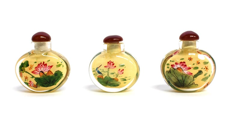 Our snuff bottles are topped with gemstone grade agate lids and 100% hand painted from within. The Chinese art of eglomise uses a very thin bamboo brush with a few strands of hair to apply watercolor on the inside walls of the blank glass bottle