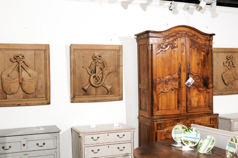 A set of three carved oak architectural panels from the 19th century, with ribbon-tied musical instruments. Created in France during the 19th century, each of these oak panels of nearly square shape, is adorned with a carved musical instrument