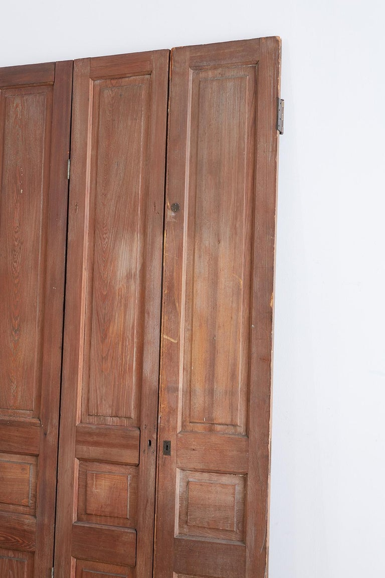 Interesting set of three conjoined French folding door screen featuring paneled design on both sides. Fully functioning and fitted with mounting hardware. One panel having a brass escutcheon but no key and a number 1 door tag. Also known as pocket