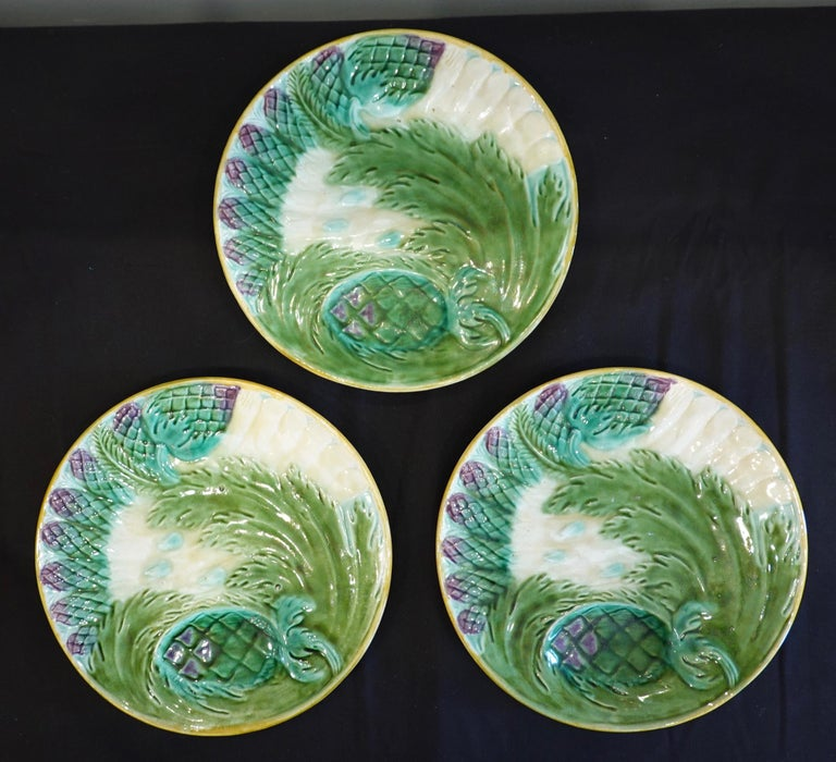 Set of three French Majolica asparagus plates by Saint Amand, (19th century). Each plate features a molded design of seven asparagus spears with an artichoke and acanthus leaf, with a depression for lemon or sauce. One plate is stamped Saint Amand,