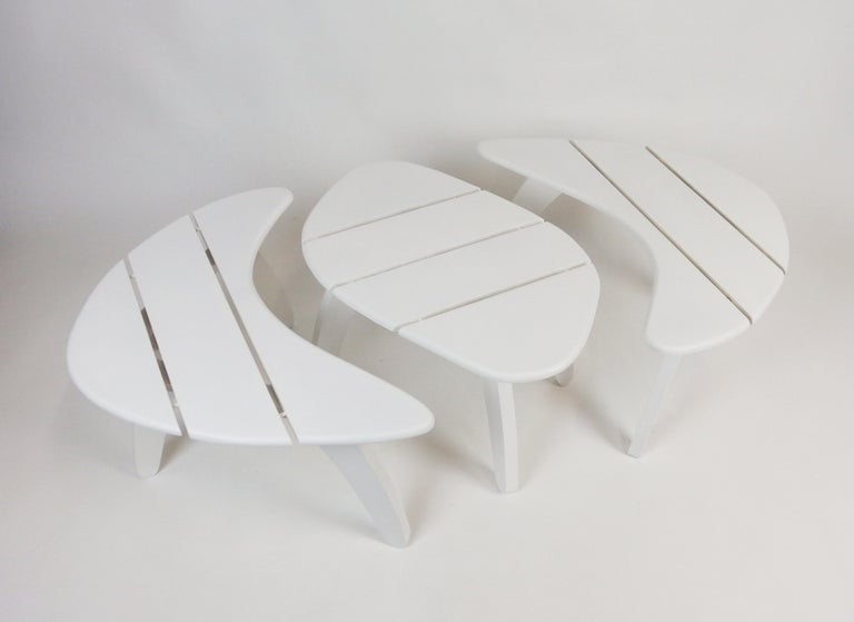 Set of three white enameled wood garden coffee tables .Two with boomerang shape tops. One with a trapezium shape top, this table connected with the boomerang shape tables on each side forming an oval table. These coffee tables were manufactured in