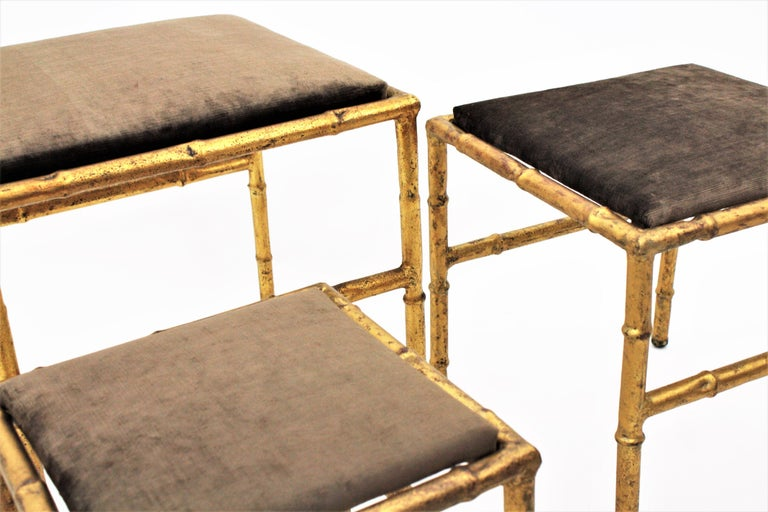 Elegant nest of gold leaf gilt iron faux bamboo stools with velvet upholstery, France, 1940s. This beautiful set of footstools have been totally refurbished in a taupe / brown / grey velvet fabric. They could also work as nesting tables changing