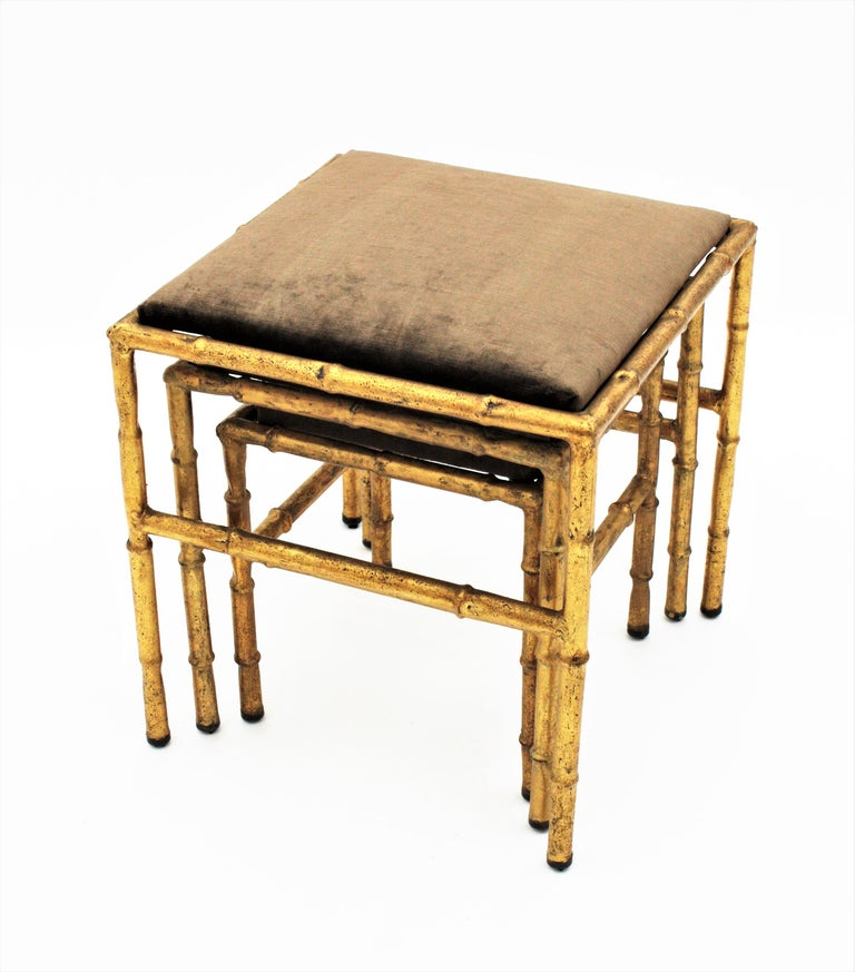 Hollywood Regency Set of Three Gilt Iron Faux Bamboo Nesting Stools Upholstered in Taupe Velvet For Sale