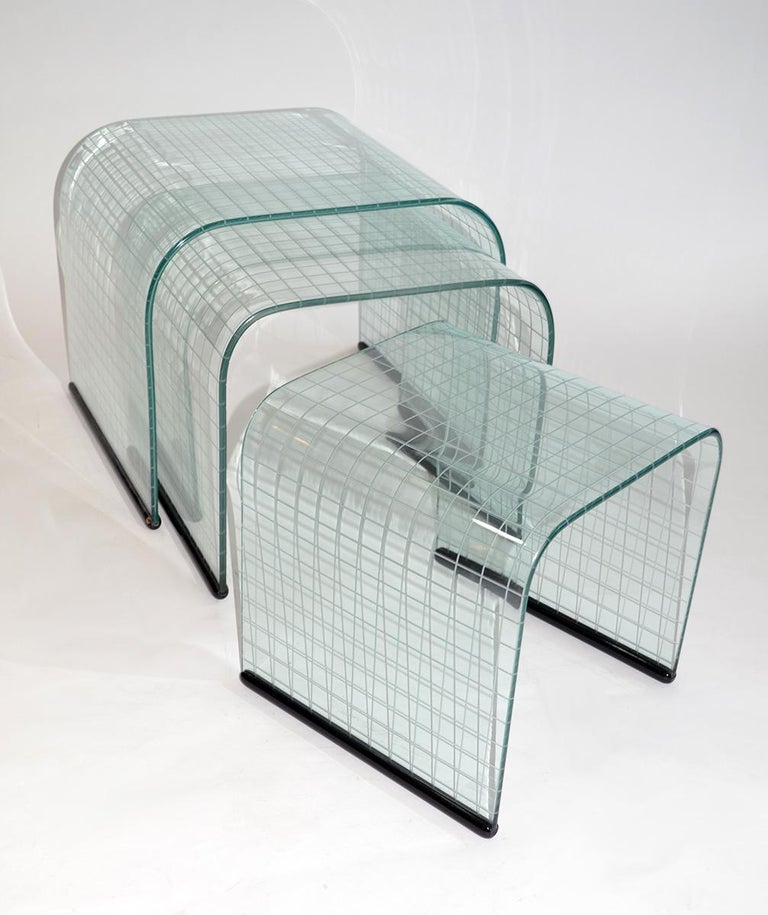 Set of three glass side nesting or stacking tables, Fiam, Italy, 1980s. Graduated side or nesting-sized with decorative reverse etched grid on plate glass with black painted wood bases. Simple, Minimalist waterfall design. Very good vintage