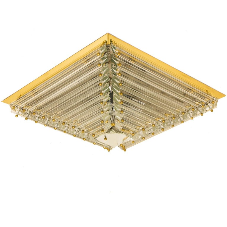 An exceptional set of three gold-plated Venini flushmounts with faceted clear crystal tubes of Murano glass. Modulated in the form of a pyramid. The flush mounts are designed and produced by Venini in Italy from the 1970s. The Murano tubes are