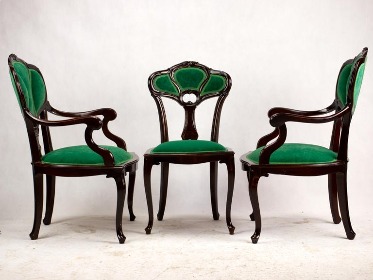 Set of three Art Nouveau early 20th century Art Nouveau armchairs. Beautifully carved chair frame made of fruitwood with upholstered seats and backrests upholstered in the shape of three leaves on cabriole legs. The chairs are completely renovated