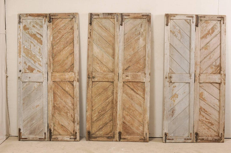 A set of three hinged-pairs of European wooden doors from the early 20th century. This collection of antique doors, standing just over 7 feet tall, are beautifully decorated with diagonally set boards within two vertical panels, down the entire