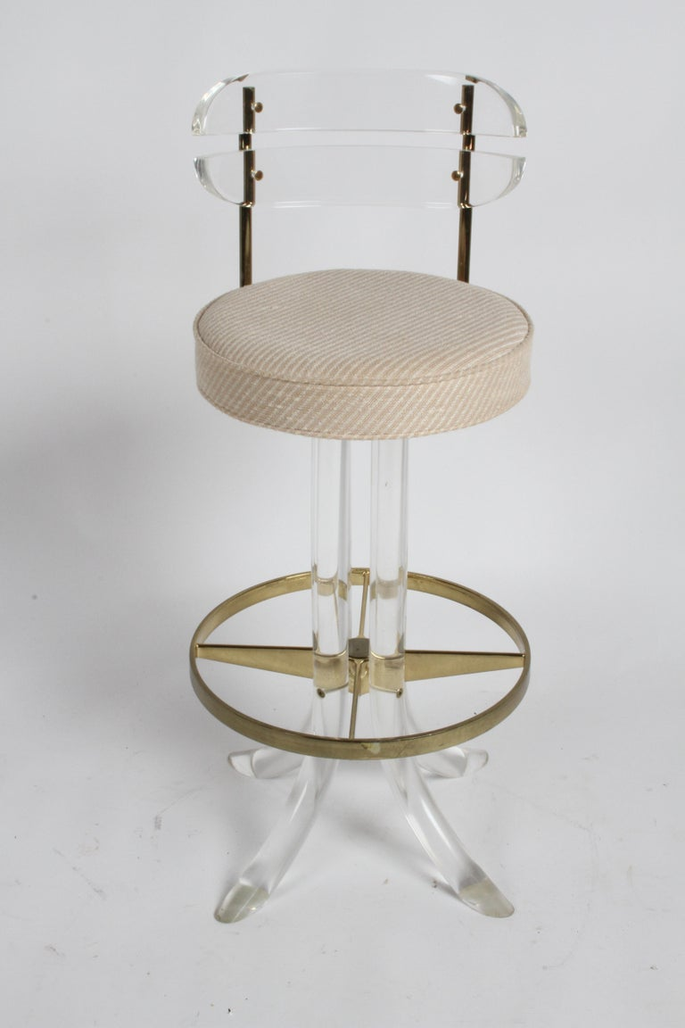 Beautiful set of three 1970s Hollywood Regency Lucite and brass bar stools with backs, foot rest and swivel by Hill Manufacturing Corp of New York. Original salmon and creme upholstery in fine condition, on thick round Lucite splayed legs. Brass and