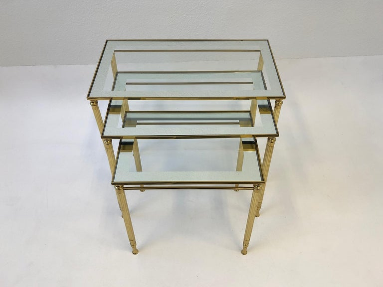 Glamorous 1970s set of three Italian brass and mirror frame glass tops nesting tables by Maison Baguès. The tables are constructed of solid brass with mirror frame glass tops. They are in original condition, so they show minor wear consistent with