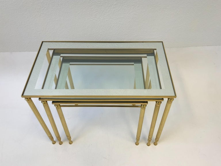 Polished Set of Three Italian Brass and Glass Nesting Tables by Maison Baguès For Sale
