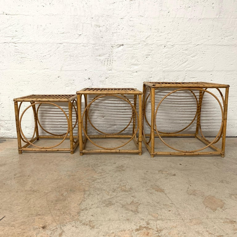 Unique set of three nesting or bunching tables in a square stacking cube shape with inset circular design, rendered in rattan, Italian attributed to Franco Albini