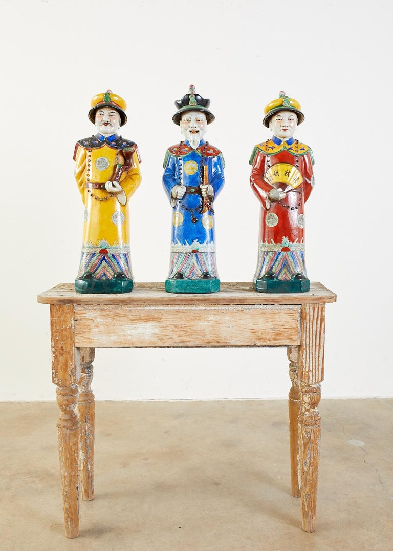 Colorful set of three large Chinese porcelain Qing emperor, royal, and monarch figural group. Beautifully glazed with a wucai style having flamboyant robes and hats. Decorated with beaded necklaces holding a flute, a fan, and a ruyi-head scepter.