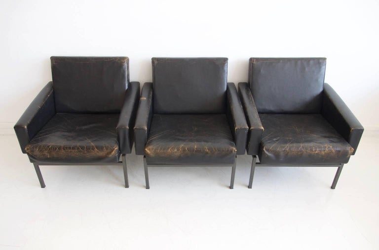 Three armchairs by Friedrich Wilhelm Moller for COR, model 'Conseta', 1970s. Original black leather with true aged patina and metal body with steel base. Frame lacquered in gray color. In the style of Arne Jacobsen's 'Airport Chair'.