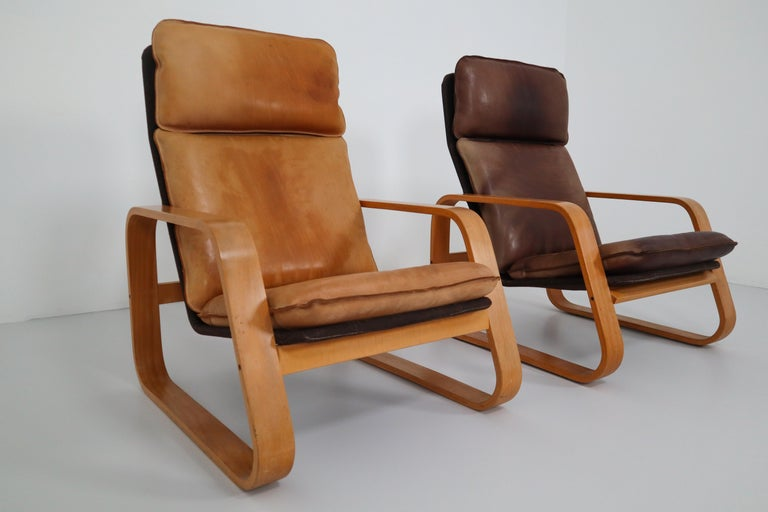 Set of three late midcentury lounge chairs, patinated leather, bentwood and fabric, France, 1970s.  These comfortable armchairs in bentwood and patinated saddle leather of this set, features a wonderful and rich patina and is therefore especially