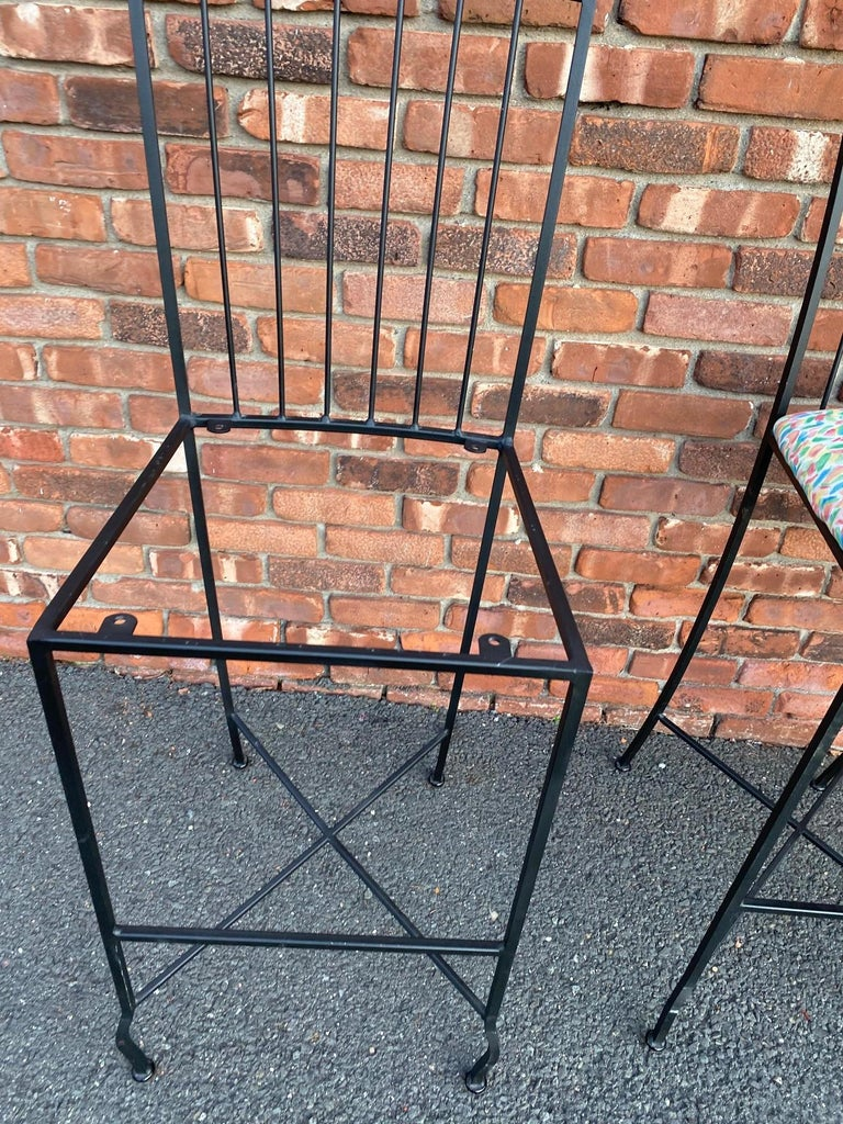 Vintage set of 3 solid metal bar stools with a removable seat cushion. They are upholstered in a whimsical cotton fabric but can easily be recovered to any style and material. There is a sturdy foot rest that is 13