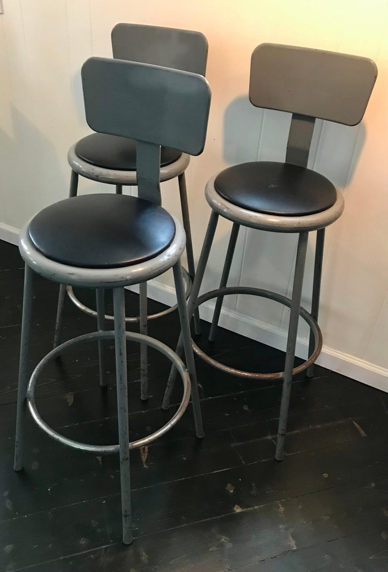 Authentic set of three Industrial bar height stools with back rests, round black vinyl seats. All original and very sturdy, wear appropriate with use, very cool. Made by Inter Royal Corporation, USA.