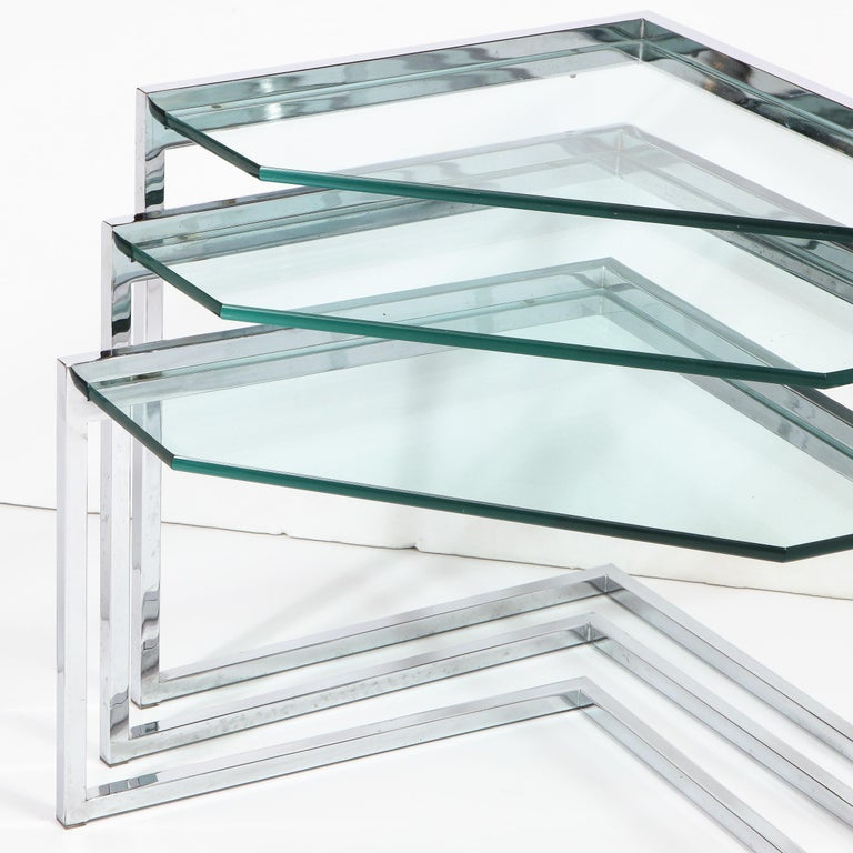 This refined set of three Mid-Century Modern nesting tables were realized in the United States, circa 1970. They feature geometric chrome frames with open form triangular bases offering right angles, that when nested created a dynamic chevron