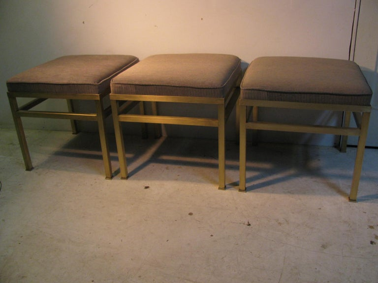 Only 1 available. Fabulous satin brass ottoman - footstool- bench. Reupholstered in a vintage style 1960s weave fabric with fabulous coloring that contrasts greatly with the brass. Square tube brass is in very good condition with no tarnish just