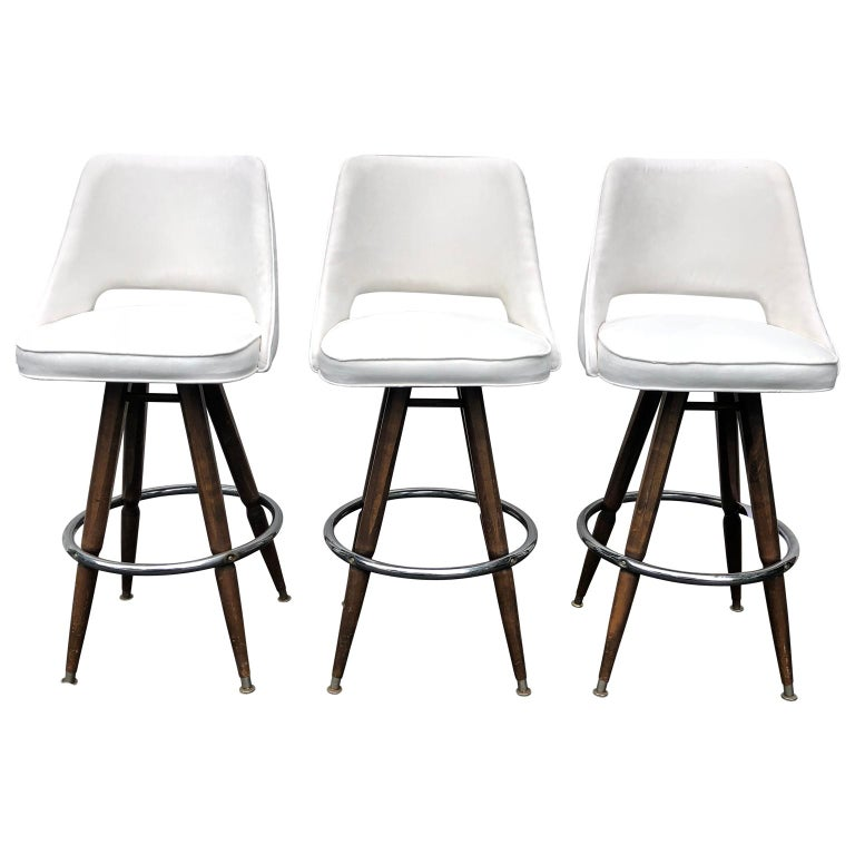 Set of Three Mid-Century White Faux-Suede Bar Stools  3 large sturdy bar stool on wooden and chrome legs. Newly upholstered in white spill-proof faux suede.