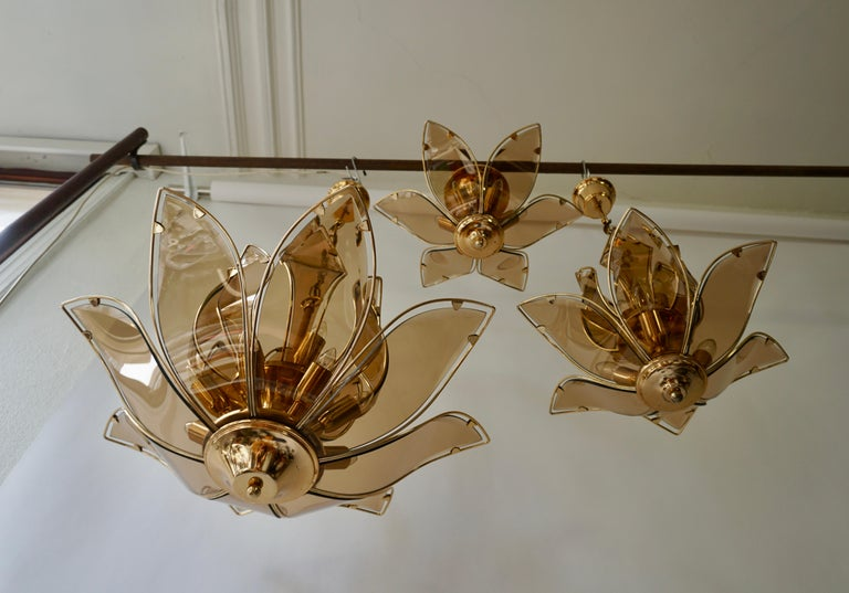 Two chandeliers and one flush mount in brass and glass. Italy 1970s. Dimensions; Chandelier: Diameter 64 cm, height fixture 50 cm, total height 85 cm. Twelve E14 bulbs. Chandelier: Diameter 48 cm, height fixture 44 cm, total height 73 cm. Six E14
