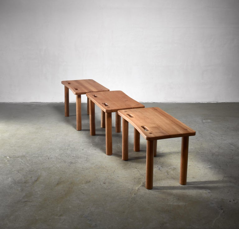 A set of three pine benches or side tables in the Campaign style known from works my Charlotte Perriand, Pierre Chapo and Roland Wilhelmsson.  They stand on thick round legs and have two grips in the seat.