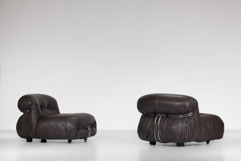 Scarpa, published by Cassina. Chromed steel structure and original brown leather seat mounted on two wheels at the front of the armchairs. Very nice vintage condition, some traces of time and use (see pictures).