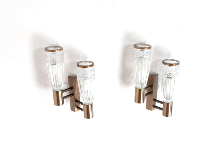 Set of three stilux wall appliques in glass, wood and metal from Italy, 1960s. These lights have an amazing design with a bronze colored base and crystal style glass. There are two items that have double lights and one that has a single light. The