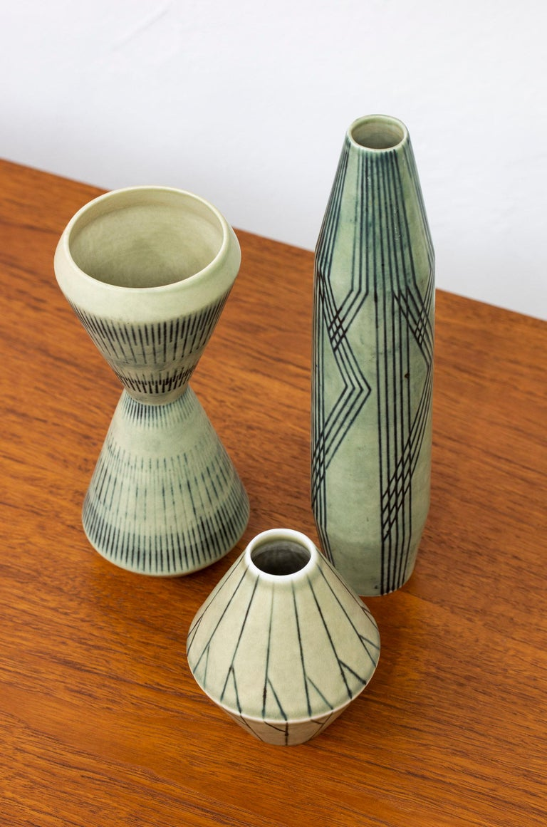 Set of htree vases designed by Carl.Harry Stålhane. hand made at Rörstrand in Sweden during the 1950s. Made from stoneware with abstract decor on light green glazes. Very good condition with light age related patina.  Dimensions: H. 11/20/25.5 Ø.