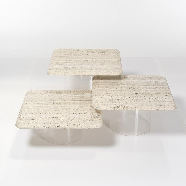A gorgeous set of three (3) nesting tables made with cylindrical Lucite bases topped by natural travertine squares with soft curved edges. Each table is 22