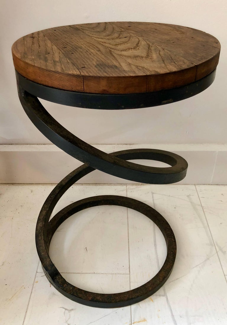 "Possibly custom-made, these rustic modern corkscrew-form tables are constructed from heavy solid wrought iron and old repurposed wood tops. All three tables are 12"" diameter; heights are 18.75"", 17.5"", and 16.75"". Sold individually."