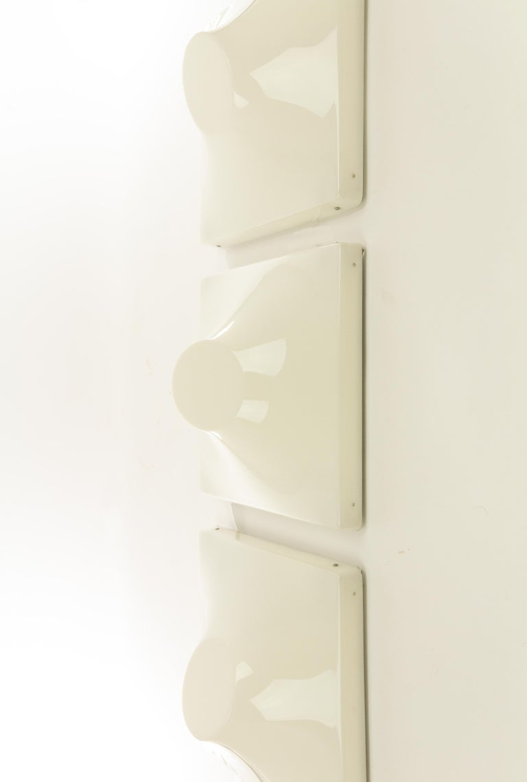 Set of three wall lamps designed by Ennio Chiggio and produced by Emmezeta in the 1970s.  The lamps consist of two parts; a metal structure that can be attached to the wall and a three-dimensional plastic front that can be clicked to the metal
