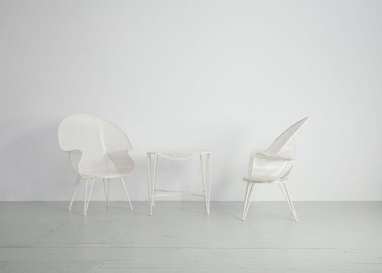 Set of three garden chairs and a fitting side table from Italy, 1950. Those armchairs of perforated plates were designed by Giuseppe De Vivo in Italy. Different rounded shapes are building the seats, which rest on straight legs. The side table comes