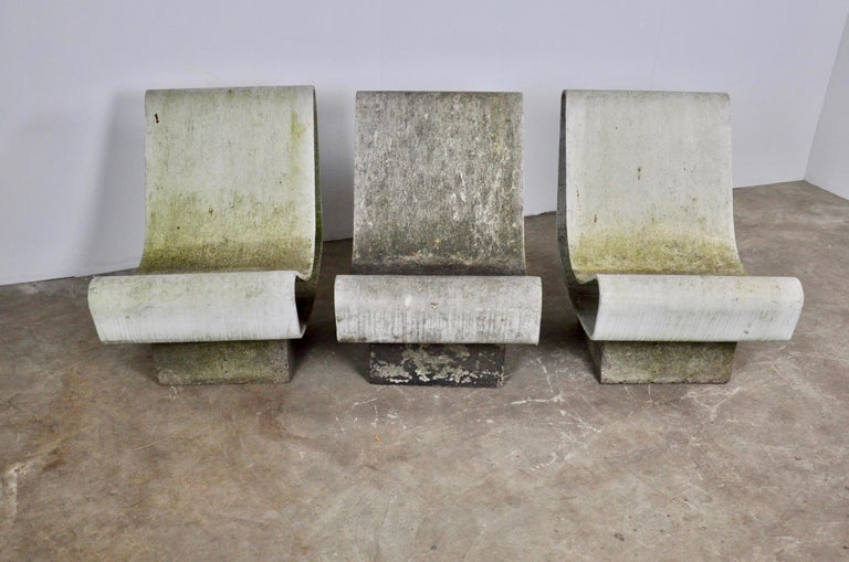 Rare set of three concrete loop chairs by Willy Guhl. Custom concrete pedestals made years ago sit underneath each chair. Great patina to chairs and bases. Chairs connect to the base with two prongs of welded rebar. Chairs can lift on and off base