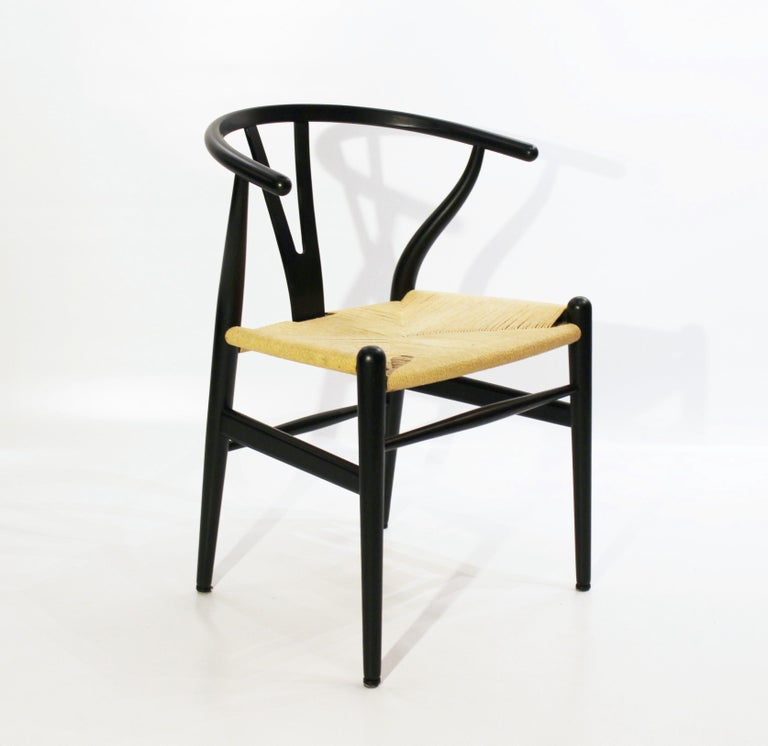Set of three wishbone chairs, model CH24, of black painted wood and paper cord designed by Hans J. Wegner and manufactured by Carl Hansen & Son. The chairs are in great vintage condition.