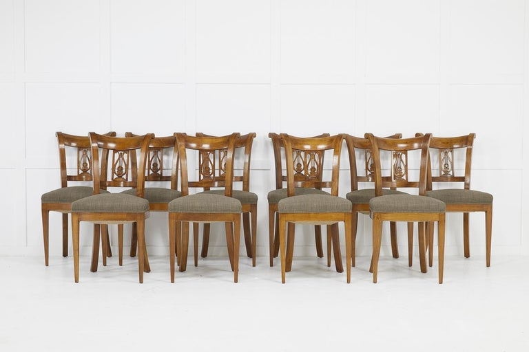 Set of twelve 19th century Austrian cherrywood dining chairs comprising two carvers and ten chairs with lyre back rests.